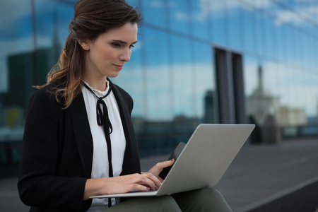 Female executive using laptop in office premises Stock Photo