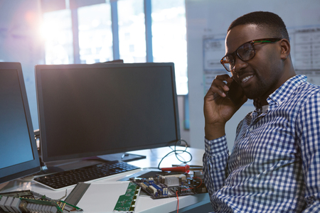Computer engineer talking on mobile phone at desk in office Stock Photo