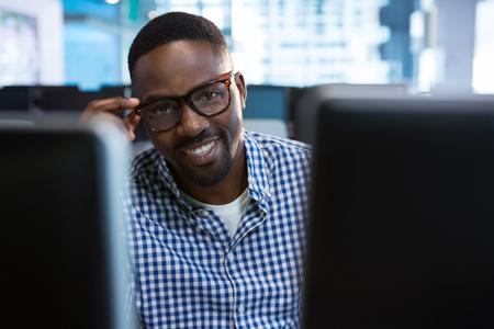 Portret van de zitting van de computeringenieur bij bureau in bureau