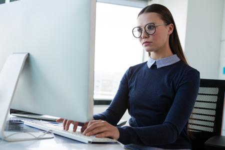 Vrouwelijke stafmedewerker die aan personal computer bij bureau in bureau werkt