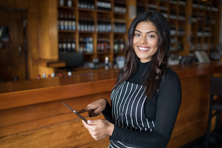 Portrait of smiling waitress using digital tablet at counter in bar Stock Photo