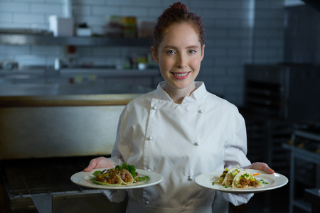 Portrait of female chef holding food plate