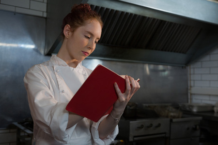 Female chef taking down an order in the book in the kitchen