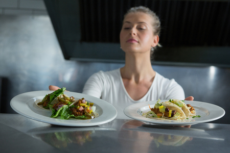 Female chef holding food plate in the kitchen