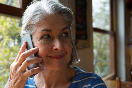 Senior woman talking on mobile phone in cafe