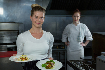 Female chefs holding food plates in the kitchen