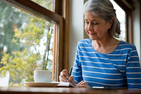 Senior woman writing in a diary in cafe Archivio Fotografico