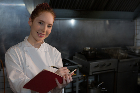 Portrait of female chef taking down an order in the book