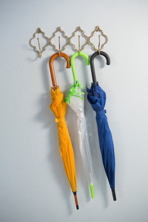 Colorful umbrellas hanging on hook against white wall Фото со стока