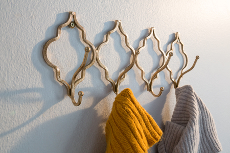 hook up: Close-up of warm clothes hanging on hook against white wall