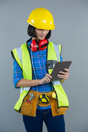 Female architect using digital tablet against grey background