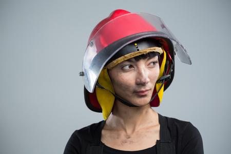 Thoughtful female architect wearing helmet against white background