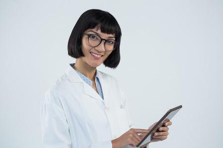 Portrait of smiling doctor using digital tablet against white background