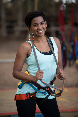 Portrait of smiling woman holding harness in park