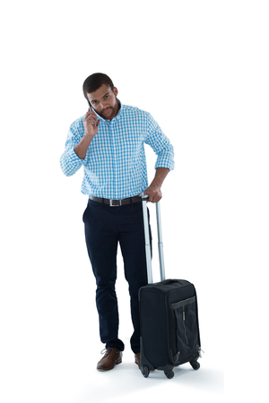 Male executive with luggage talking on mobile phone against white background Stock Photo