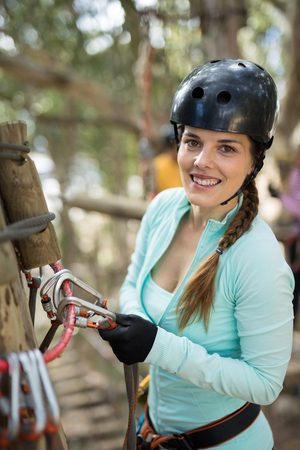 Smiling woman holding carabiner in park Stock Photo