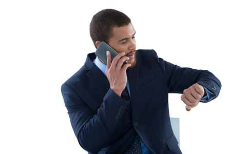 Young businessman checking time while talking on mobile phone