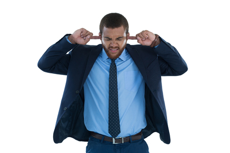 Irritated businessman covering his ears against white background Stock Photo
