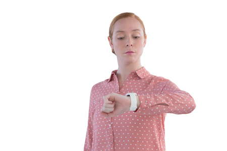 Young female executive looking at wristwatch Stock Photo