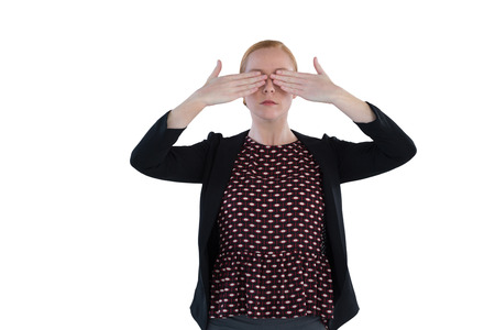 Woman covering both her eyes against white background
