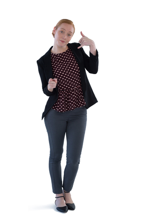 Young female executive gesturing against white background