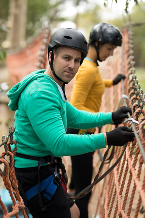 Couple attaching carabiner on rope bridge on a sunny day Stock Photo