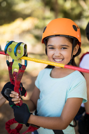 Smiling cute girl enjoying zip line adventure on sunny day Stock Photo