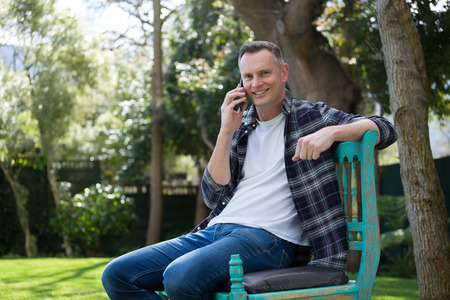 Man talking on mobile phone in garden on a sunny day