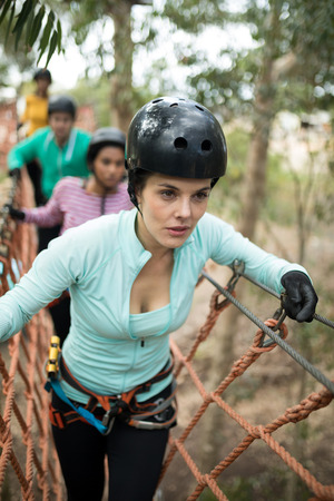 Beautiful woman walking on rope bridge