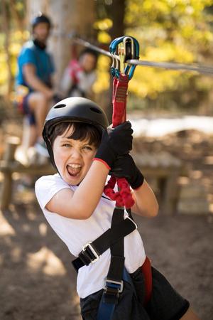 polea: Smiling cute boy enjoying zip line adventure on sunny day