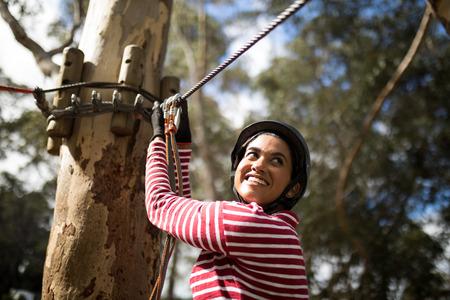 polea: Mujer sonriente lista para tirolesa en el parque de aventura en un día soleado Foto de archivo