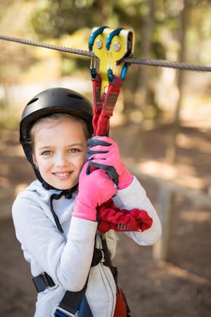 Smiling cute girl enjoying zip line adventure on sunny day Imagens