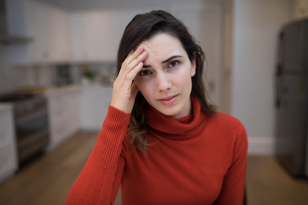Portrait of beautiful woman suffering from headache at home