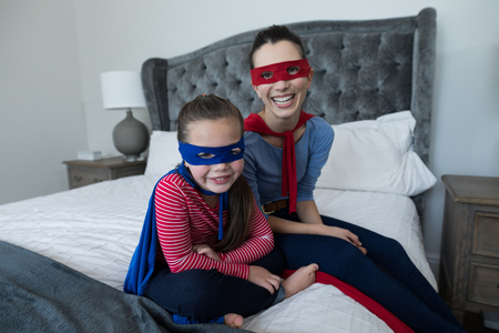 Portrait of mother and daughter pretending to be superhero
