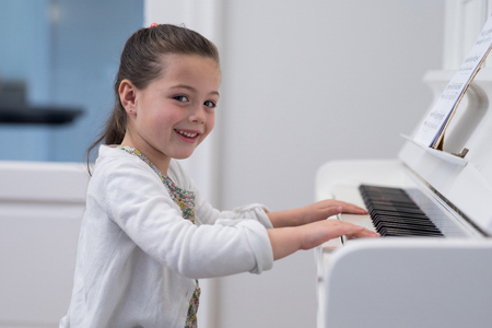domicile: Portrait of cute girl playing piano at home