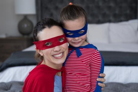 Mother and daughter pretending to be superhero in bedroom