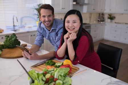 Smiling couple leaning on the kitchen worktop with vegetables in front