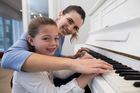 Portrait of mother assisting daughter in playing piano at home