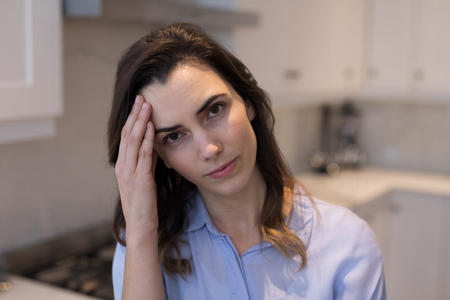 Woman suffering from headache in kitchen at home