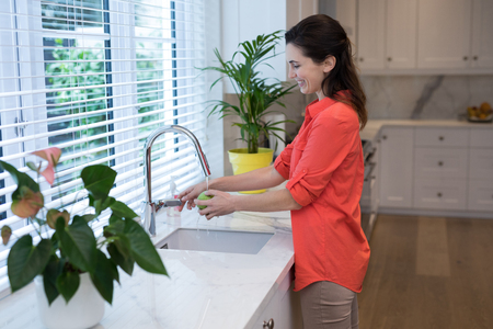 Woman washing fruit in kitchen at home