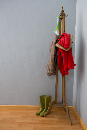 Umbrella, warm clothing and wellington boots arranged on wooden stand Stock Photo
