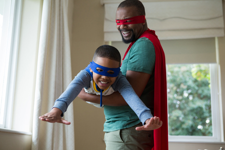 domicile: Smiling son and father pretending to be a superhero at home Stock Photo