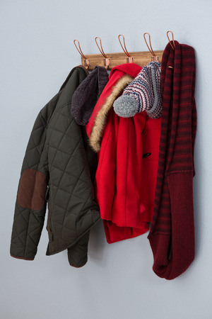Warm clothing hanging on hook against wall