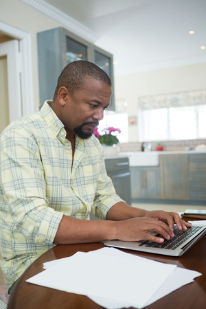 domicile: Man using laptop in kitchen at home