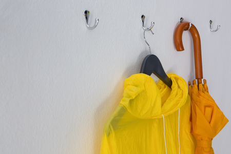 hook up: Close-up of raincoat and umbrella hanging on hook Stock Photo