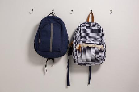 Schoolbags hanging on hook against wall Banco de Imagens