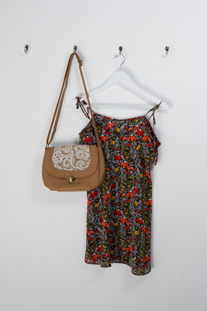 Dress and bag hanging on hook against wall