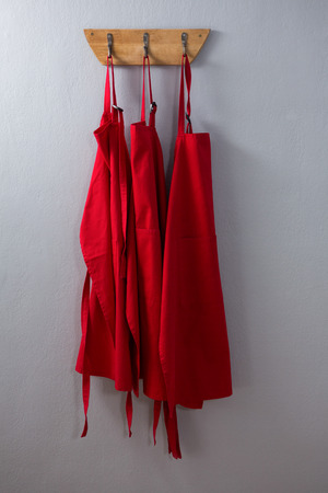 Red aprons hanging on hook against wall