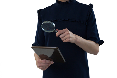Mid section of female executive holding magnifying glass and digital tablet Stockfoto