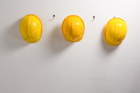 Hard hats hanging on hook against wall